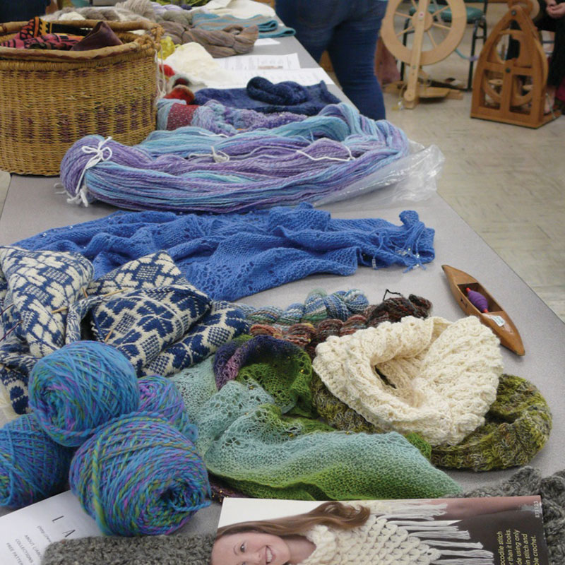 Handspun and handknitted items laid out on the Peachtree Handspinners Guild show-and-tell table during a monthly meeting, surrounded by the spinning circle. Photo courtesy of Peachtree Handspinners Guild.