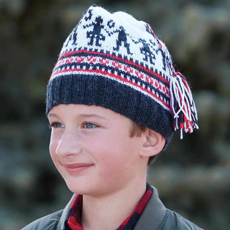 """Susan Strawn's knitted cap """"Norwegian Barnelue to Knit"""" will delight the younger set. The dancing couple plus the stripes and tiny geometric patterns are traditional Norwegian motifs. Photograph by George Boe."""