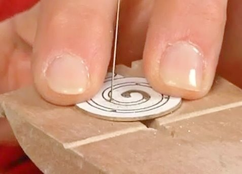 drill holes and saw a spiral from metal sheet