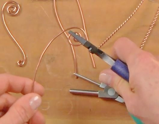 steer wire with hand around pliers to make spirals