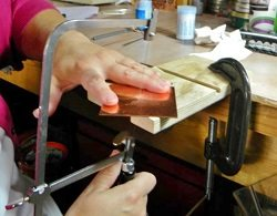 Keep the jeweler's saw stationary and turn the piece that is being sawed as you'll have more control over where the saw cuts. Read more sawing metal tips!