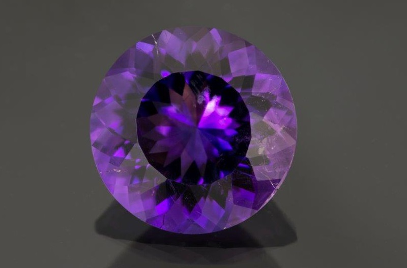 amethyst gemstones: Inclusions like those visible in this 8.34 carat round amethyst are indicative of a natural stone. Photo Mia Dixon. Courtesy Pala International.