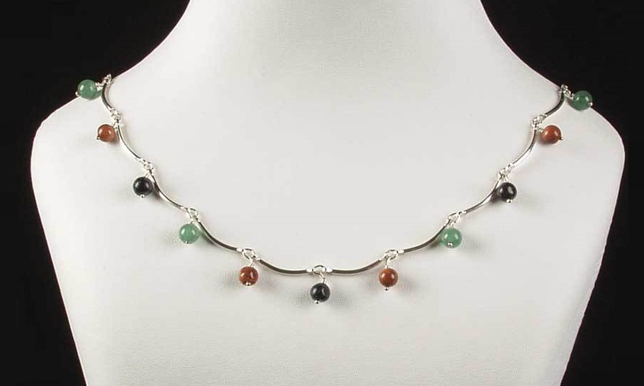 Aventurine in many colors dot this curved sterling silver curved bar necklace.