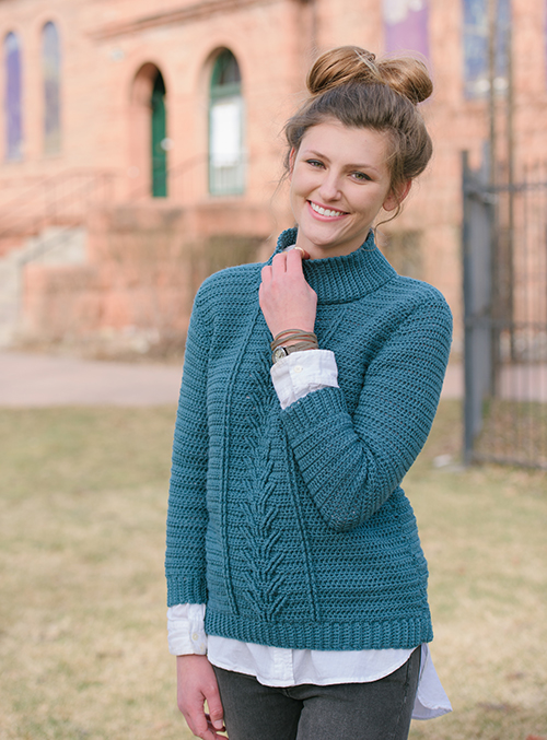 Sleeve of Botany Pullover crochet sweater has cables