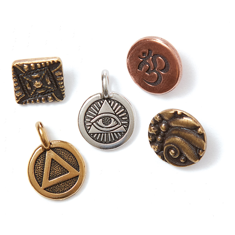 TierraCast has released a line of charms and mini buttons featuring symbols representing strength and beauty.
