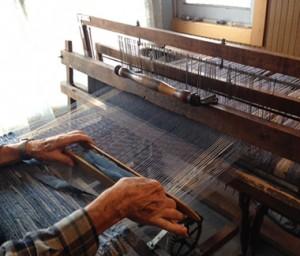 Charley weaving a denim rag rug on his loom.