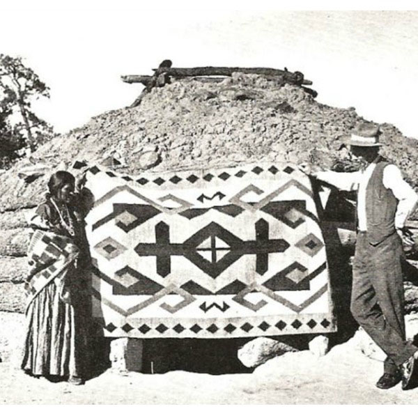 A Dinè (Navajo) weaver poses with J. B. Moore and her rug at the Crystal Trading Post, circa 1911.