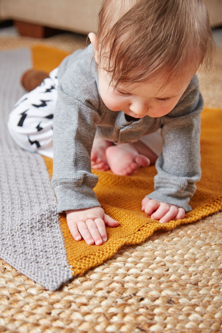 You'll making this knitted baby blanket that breaks up the large sections of stockinette and double-moss stitch with two colors and two textures!