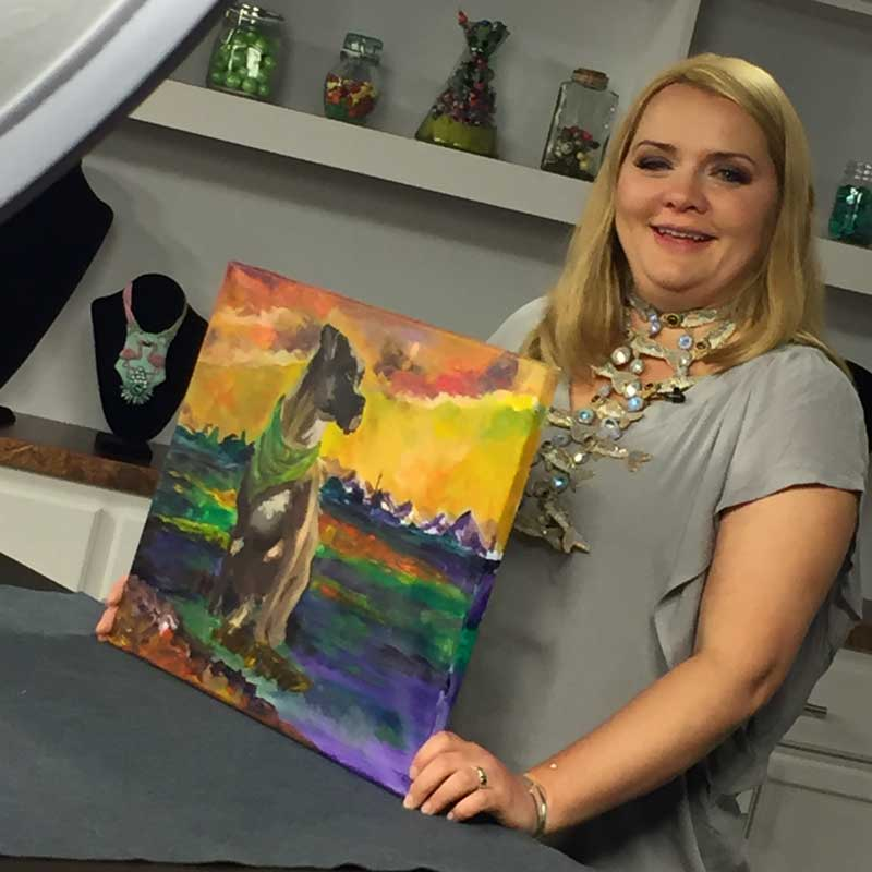 Kinga Nichols on set with a painting she did of her dog, Sammy