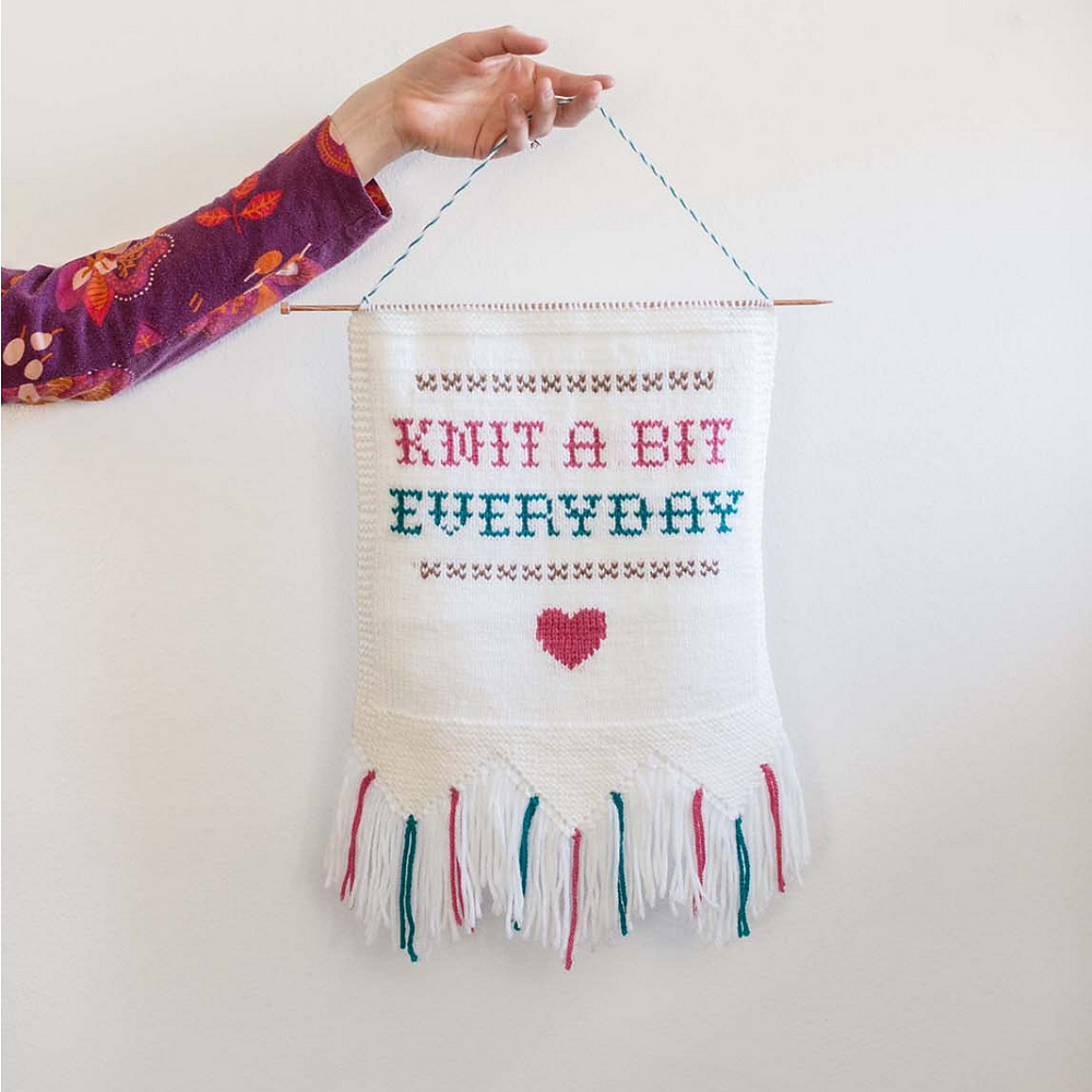 You can customize this handknit wall hanging with any phrase you like.