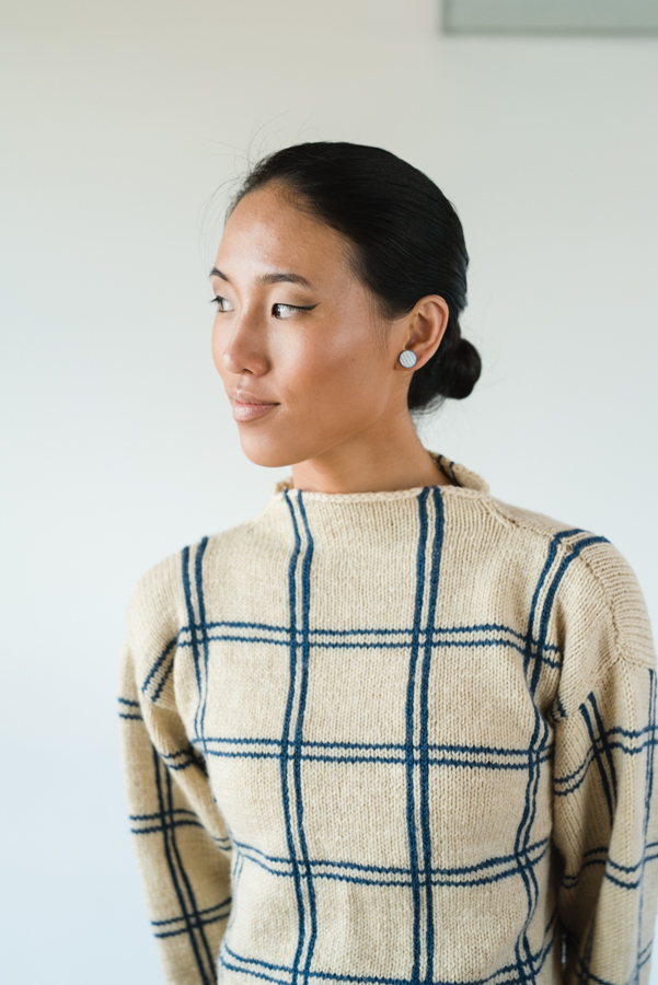 You'll love this knitted sweater pattern that includes double vertical & horizontal lines set against a plain background creating a minimalist plaid.