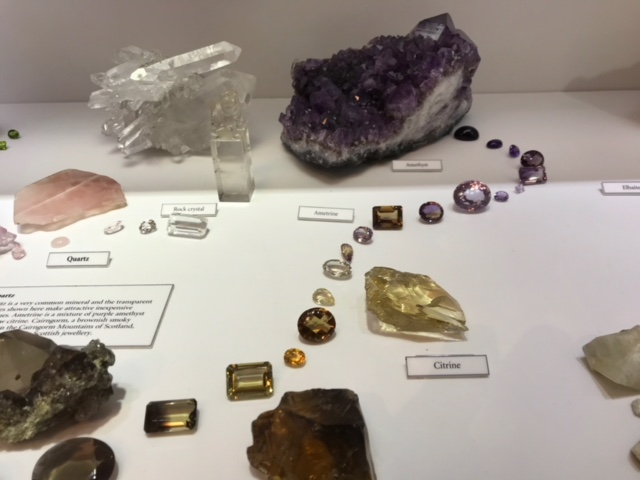 A display of quartz gemstones shows an excellent range of colors and varieties, including rock crystal with lepidocrocite inclusions. Collection Oxford University Museum of Natural History.