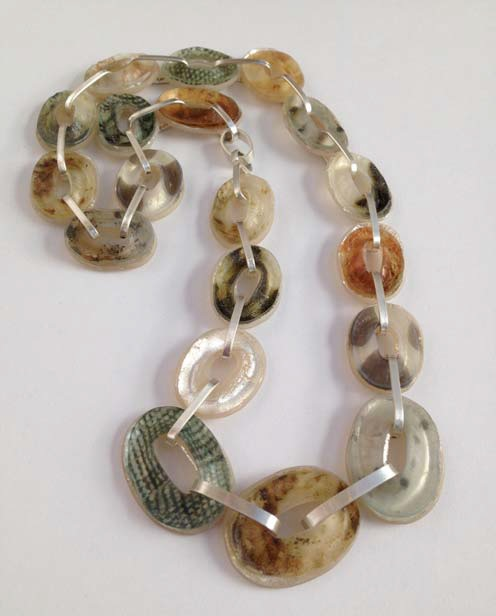 The ovals in this necklace have a shimmery quality that comes from layering elements during construction. The lower layer has been silver leafed; the upper is a thin layer of polymer and a transfer. As light goes through the top layer, it's reflected from the silver leaf, which illuminates the clay and makes it glow. Photo: Sarah Wilbanks.