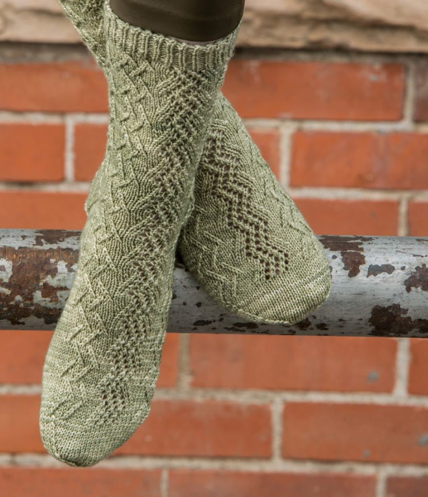 Lace and traveling stitches meet in the gorgeous Thyme Marches On sock knitting pattern.