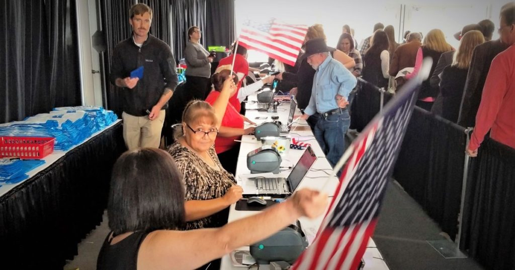 Registration clerks use American flags to wave a line of customers forward at the G&LW Holidome show on opening day.