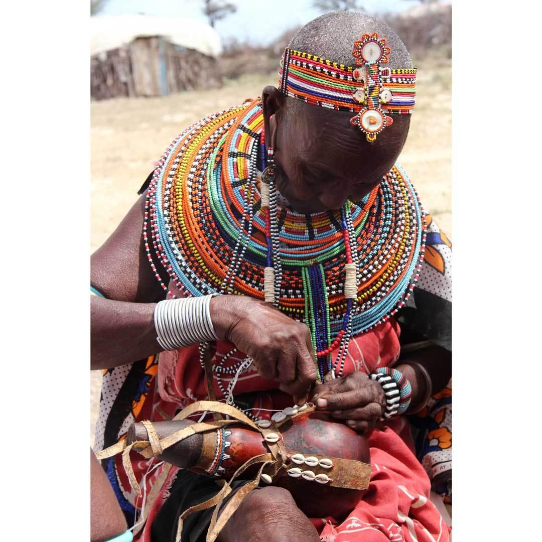 Ngamasioi Lembwakita adding cowrie shells to a milk gourd; photo credit: Brett Bruyere