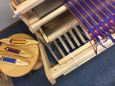 Carrying multiple wefts: a. Place the shuttles on a stool or table at the side of the loom.