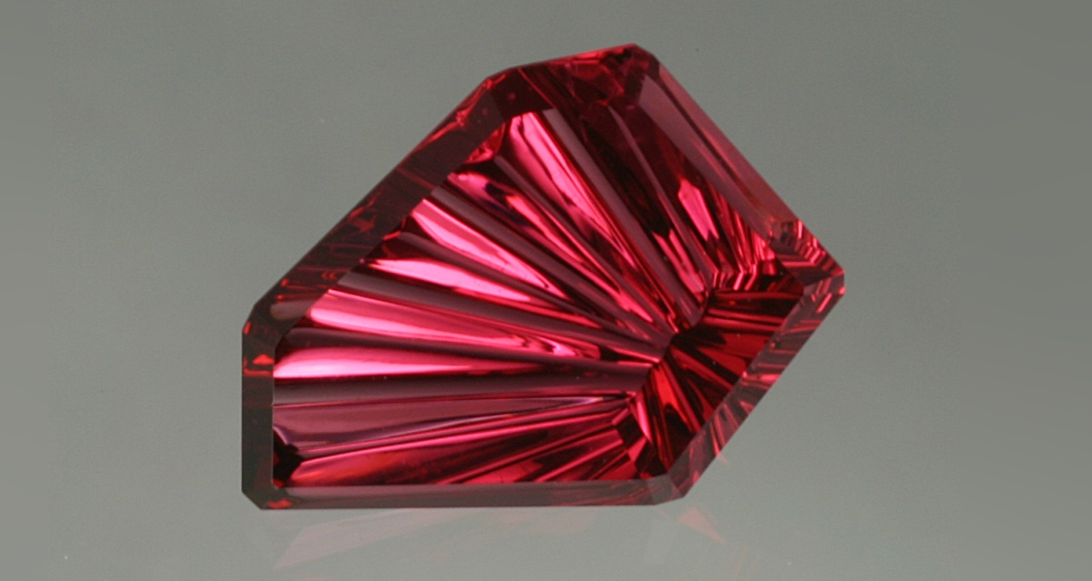 John Dyer's 3.24 ct DreamScapeTM rhodolite garnet. While garnet's a common gemstone material, rhodolite's not. This one has particularly impressive color and is oh-so-uncommonly cut! Photo: Lydia Dyer