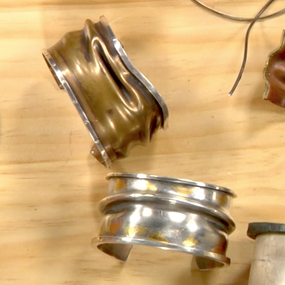 The upper cuff has an edge that has been riveted on, while the lower cuff has a soldered edge.