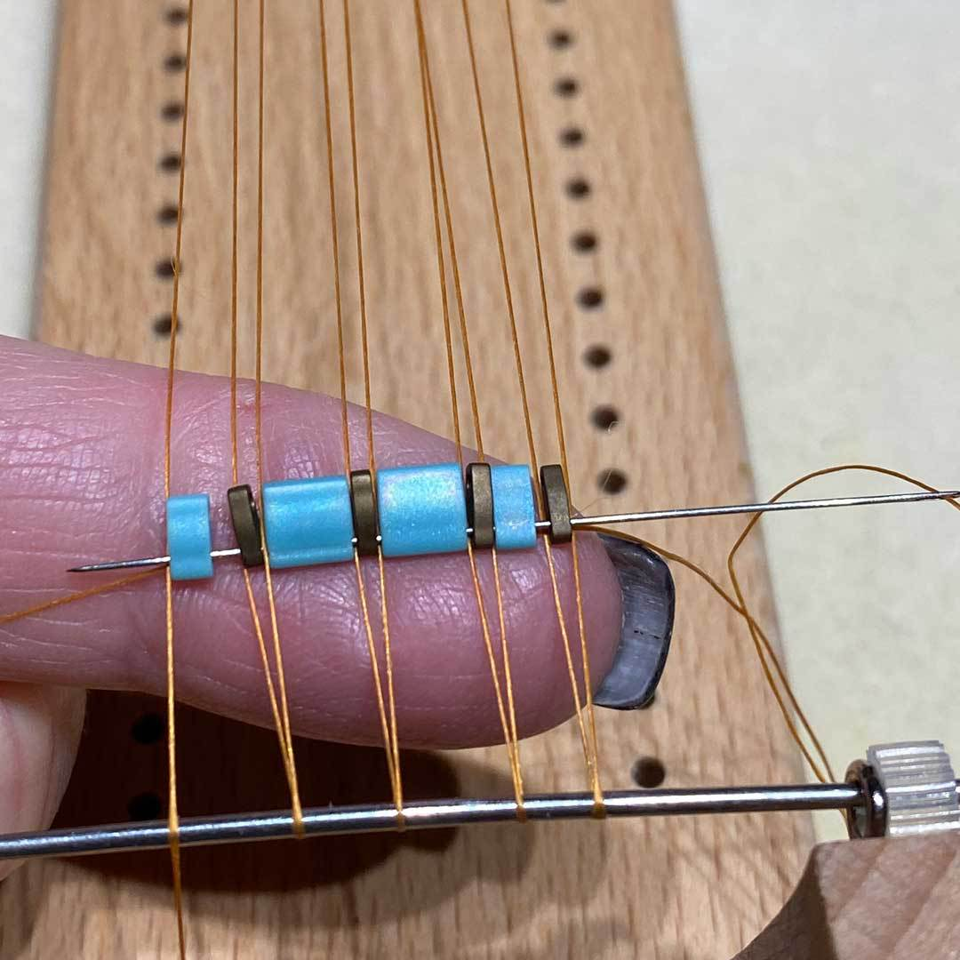 Hold the beads in place then pass the needle back through the beads, working over the warp threads. This over and under the warps is what holds the beads in place.