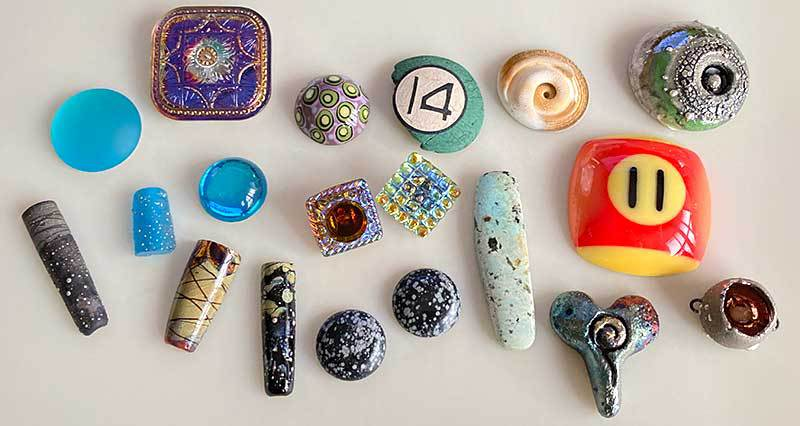 An assortment of focal options, including Czech glass buttons, gemstones, lampwork cabochons, raku components, and pool ball cabochons.