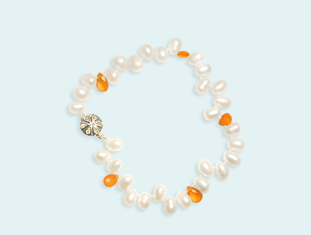 Punctuating this bracelet of off-center-drilled, egg-shaped pearls, orange carnelians give the strand a burst of sunlight. Photo by Matthew Arden, courtesy Eve J. Alfillé Gallery and Studio Evanston, Illinois.