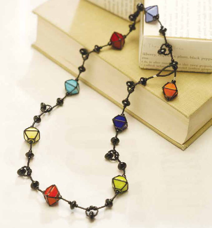 Learn how to make a necklace with glass beads using the string beading technique.