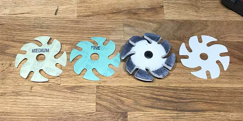 Left to right: Diamond abrasives 45 and 20 microns, felt disc with polishing compound, and cerium oxide abrasive