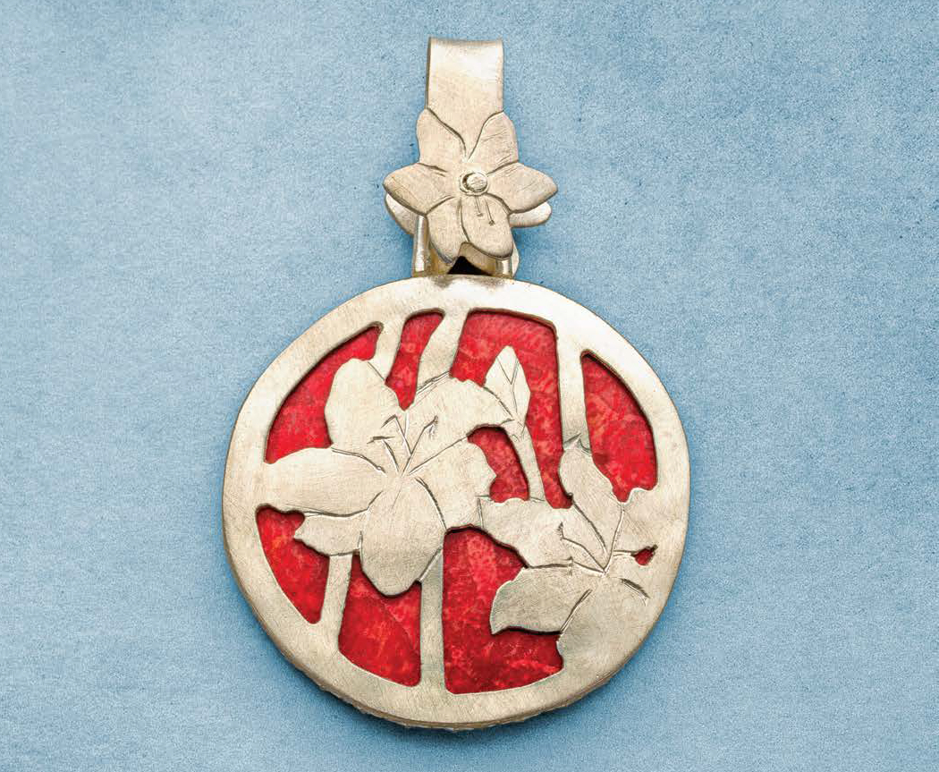"When she found this coral cab, Peggy Haupt wanted to show it off with just a gallery wire bezel, then decided to add silver flowers across the open ""back"" of her reversible pendant; photo: Jim Lawson. Lapidary Journal Jewelry Artist"