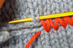 The sixthstep in the mattress stitch includes laying the second knitted piece parallel to the first.