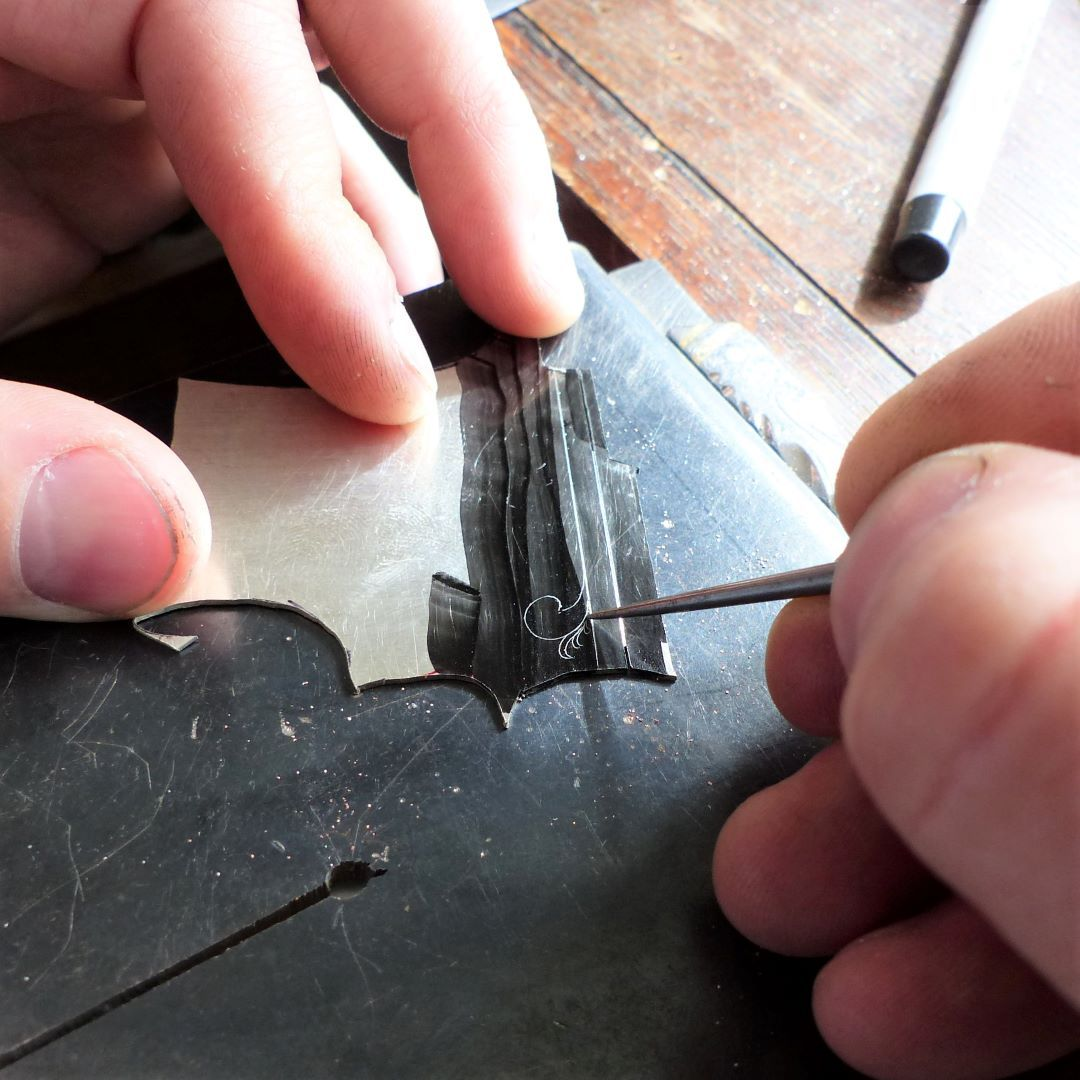 Holding a super sharp scribe, Jake draws guide lines through the ink.