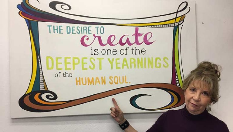 Metal clay artist Darlene Armstrong poses near an inspirational sign in her studio.