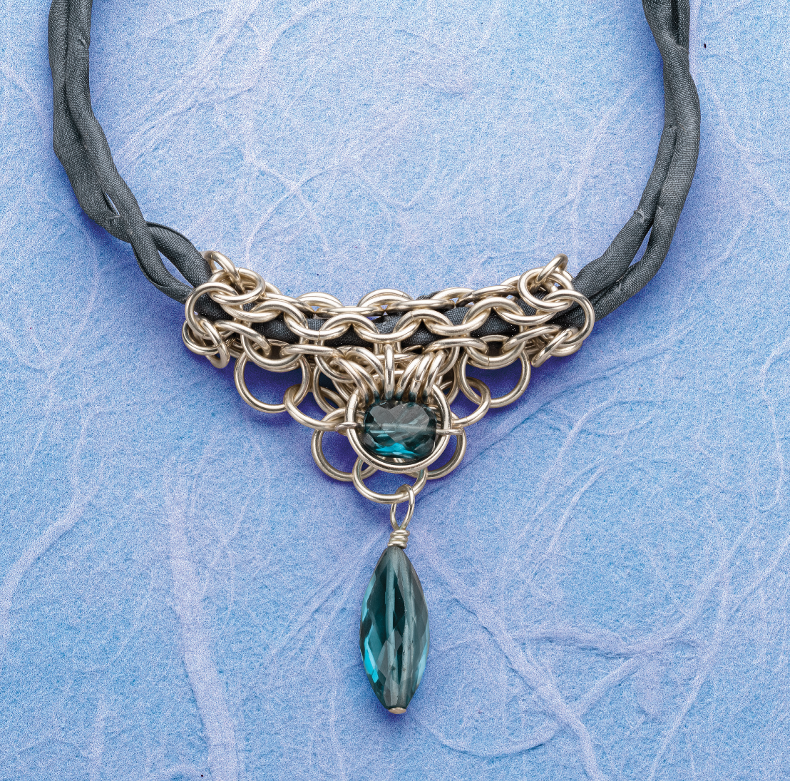 Kylie Jones draws on interest in fashion and a fascination with the patterns that can be created by linking rings. She also frequently shares her patterns and explains her process with others, including this Celebrate Blue topaz chain maille necklace project in Lapidary Journal Jewelry Artist May/June 2019. Photo: Jim Lawson