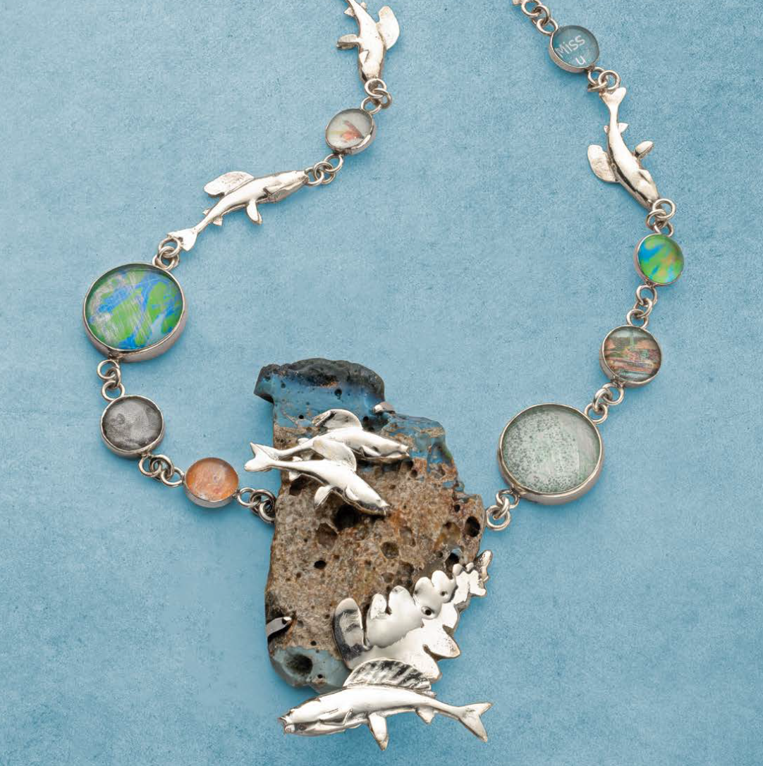 This concept necklace invokes the artist's home state of Michigan with local trout, evergreens, photo images, and Leland Blue, a byproduct of area mining; photo: Jim Lawson. Lapidary Journal Jewelry Artist