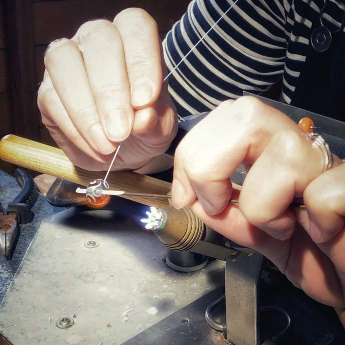 Laura Sparling uses steady hands to melt thin glass stringer onto a hot bead in the flame.