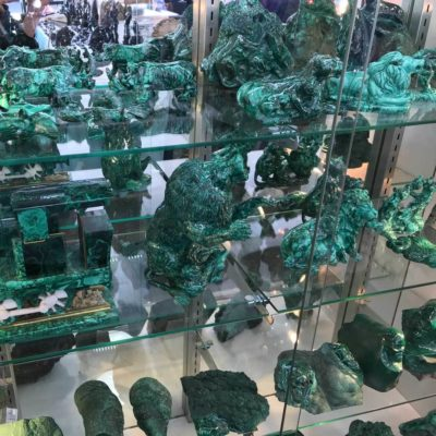 A display case filled with malachite and intricate carvings at the Pueble Gem & Mineral Show.