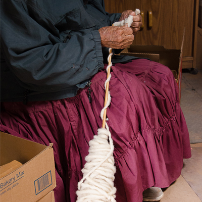 At the age of 93, Rena Lane still spins wool on her Navajo spindle. Photo by Jennifer Bauman