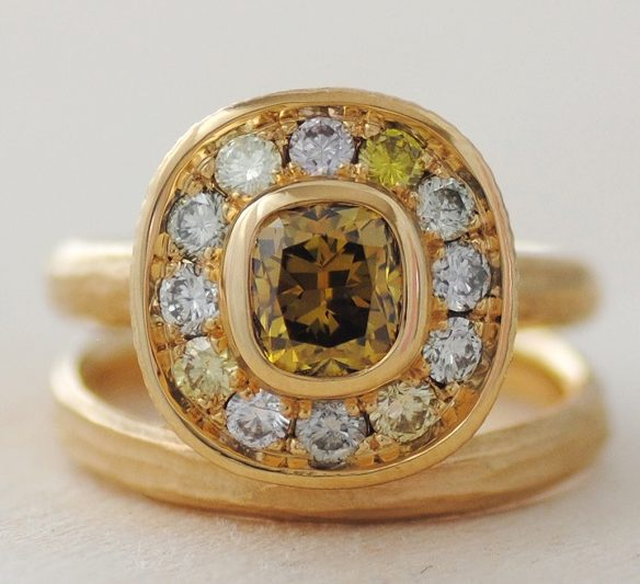 """Yellow diamonds come in all tones, from very difficult to detect through pale yellow to deep """"canary."""" Several light yellow diamonds surround the center stone in this ring by Michael Endlich that would be graded on the GIA color scale. (The light pink diamonds in the halo are always considered fancies.) However, the tone of the 1.09 carat brownish-yellow center stone is dark enough to be considered a fancy color. The 18k yellow gold mounting enhances the intensity of the stones. Design by Michael Endlich, photo by Sarah Francis, courtesy Pavé Fine Jewelry."""