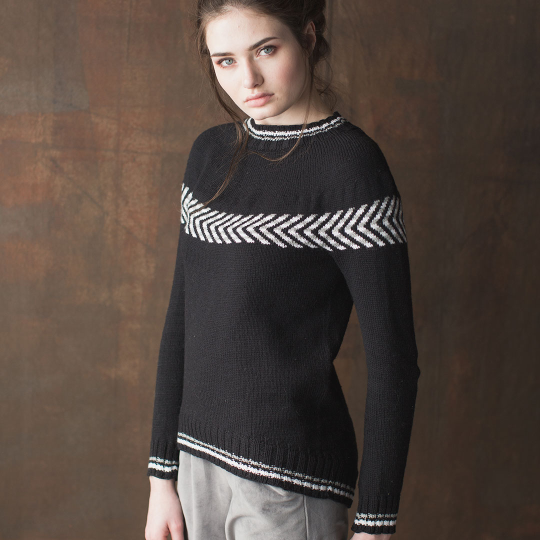 The Pepper and Snow Pullover by Cheryl Toy features small sections of stranded colorwork, accompanied by allover in-the-round stockinette-stitch in one color, down the arms and body.