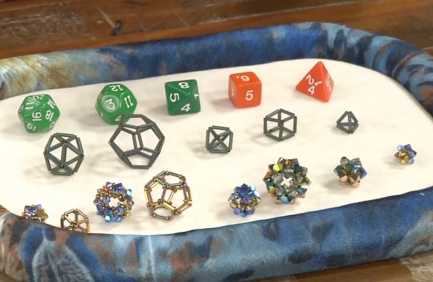 Cindy Holsclaw shows examples of Platonic solids. From left to right: icosahedron, dodecahedron, octahedron, cube, and tetrahedron.