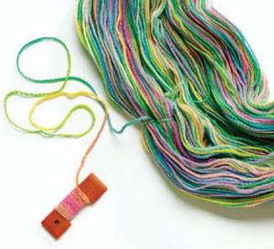 Plying Chained Singles is an article written by Dodie Rush and teaches spinners a new yarn spinning technique. The colorful yarn in this photo is attached to a spindle.