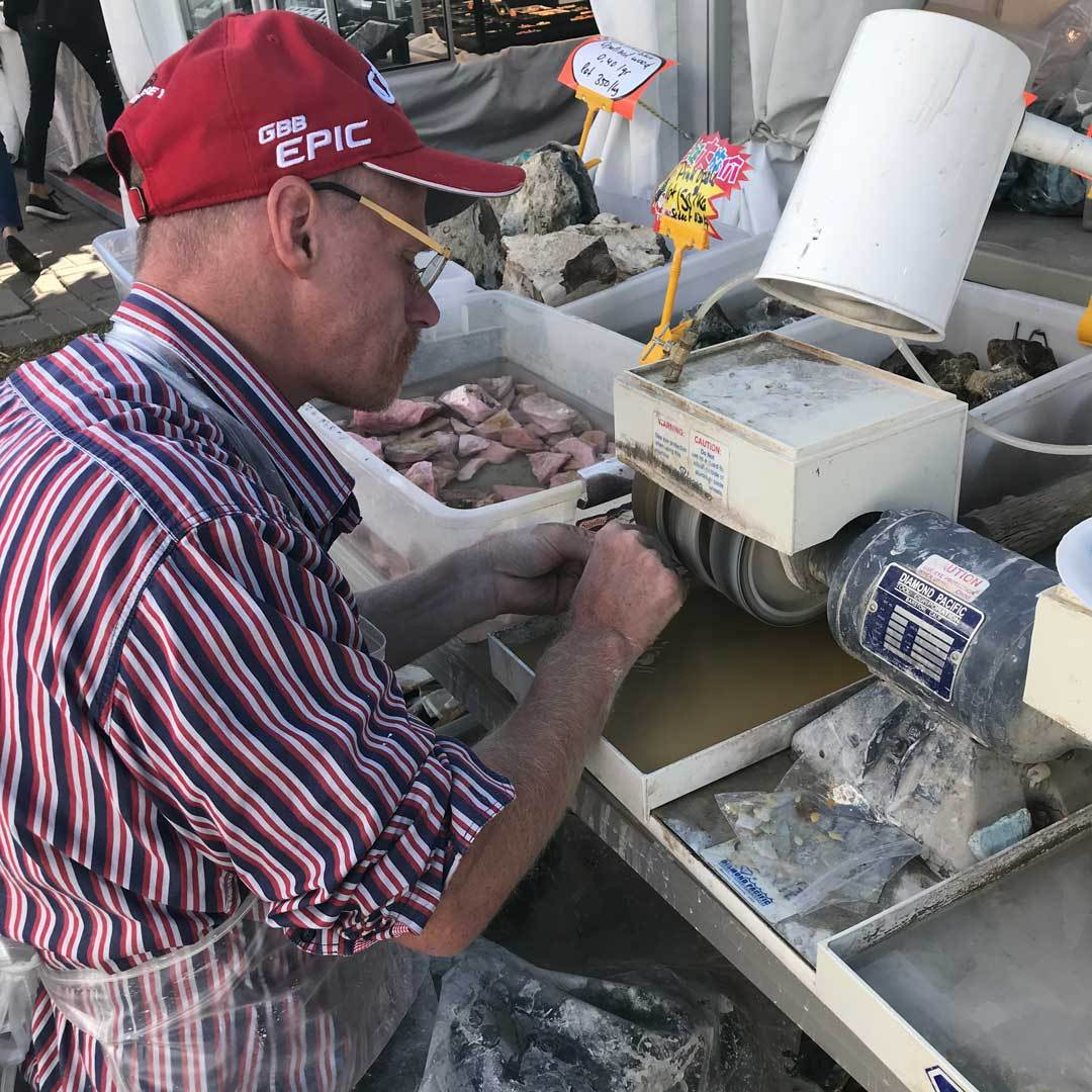 polishing rough gem material outside in Tucson