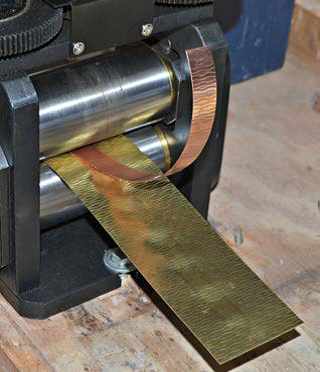 Running a piece of copper with a brass texture plate through a roll mill; photo: Jeff Fulkerson
