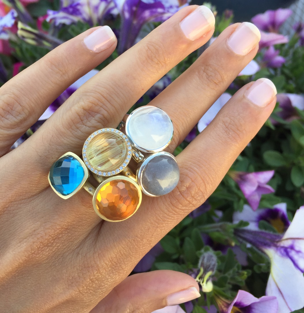 "What's making designers go ""Over the Moonstone"" for this gently glowing gem? Find out in Trends. Rainbow and gray moonstone, rutilated quartz, citrine, and blue topaz rings by Shamila Jawa; photo courtesy Shamila Jawa"